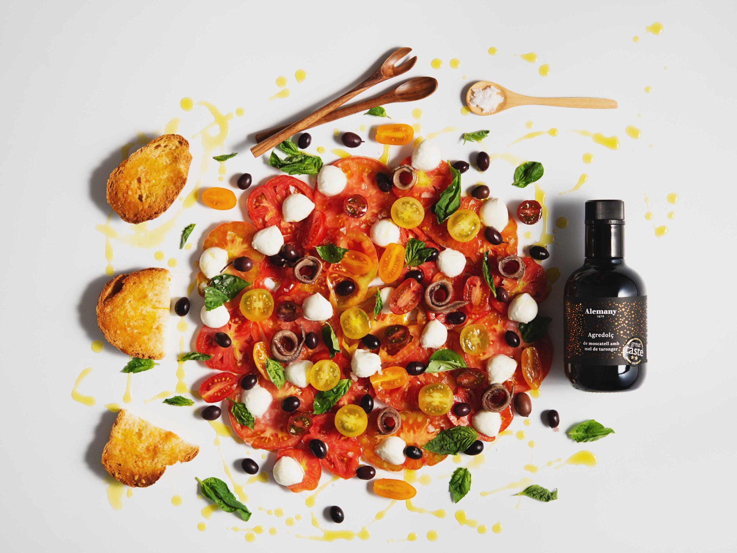 Amanida de tomàquet amb anxoves i mozzarella regada amb agredolç de moscatell amb mel de taronger